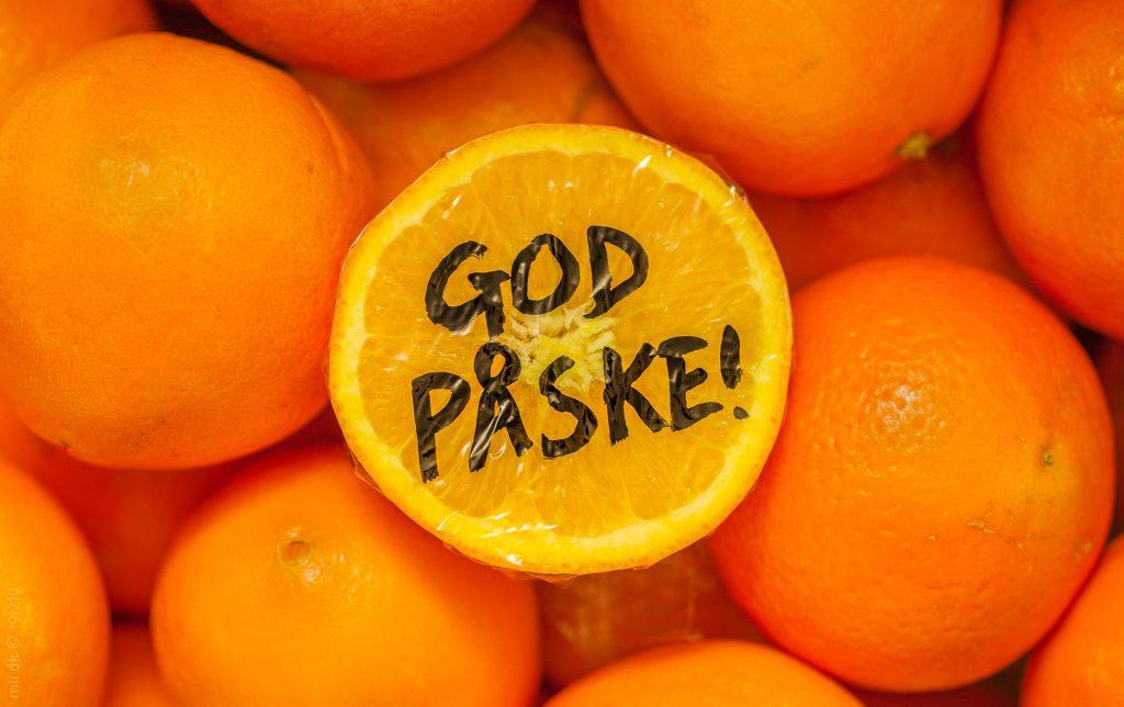 """Påskehilsen med """"God påske!"""" skrevet på en afskåret appelsin, der ligger på en seng med appelsiner."""