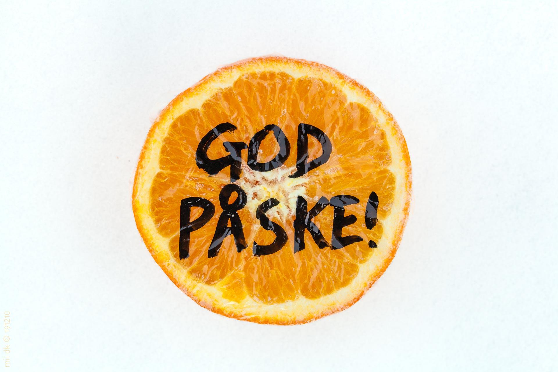 """Påskehilsen med """"God påske!"""" skrevet på en afskåret appelsin, der ligger på sneen."""