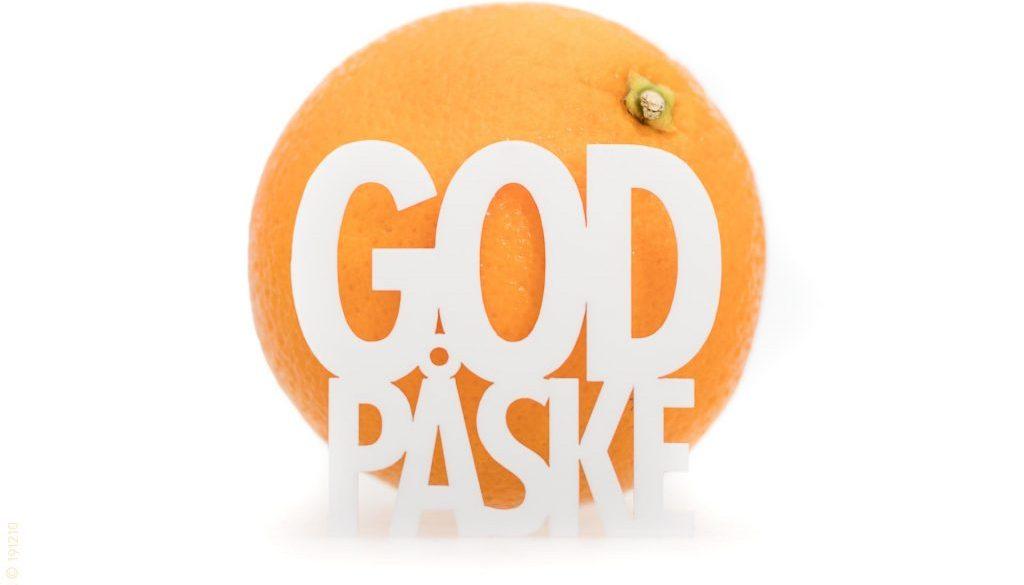 Dansk tekst 'God påske' foran en appelsin. Hvid baggrund.